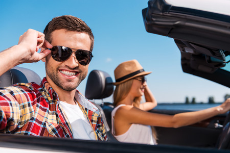 Couple in convertible. Beautiful young couple enjoying road trip in their convertible while handsome man adjusting his sunglasses and smiling photo