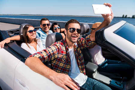 capturing: Capturing fun. Group of young happy people enjoying road trip in convertible and making selfie