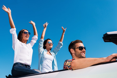 Enjoying road trip. Three young happy people enjoying road trip in their white convertible while two beautiful woman raising arms and smiling photo