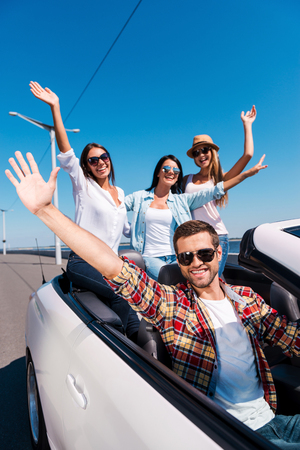 Fun travel. Group of young happy people enjoying road trip in their white convertible and raising their arms up photo