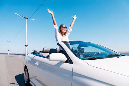 Couple in cabriolet. Happy young couple enjoying road trip in their convertible while woman raising arms and smiling  Standard-Bild