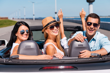 Friends in convertible. Group of young happy people enjoying road trip in their convertible while three of them looking over shoulder and smiling photo