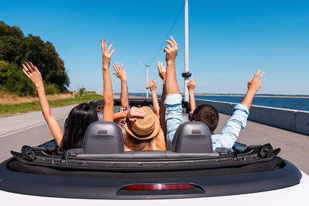 Just fun and road ahead. Rear view of young happy people enjoying road trip in their convertible and raising their arms up Stockfoto