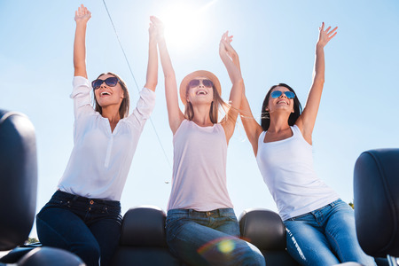 What a great day! Low angle view of three beautiful young women enjoying road trip in convertible and raising their arms photo
