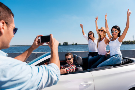 photography themes: Capturing happy moments. Rear view of young man photographing his friends sitting in convertible  Stock Photo