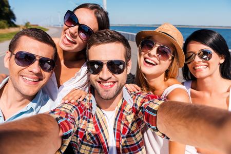 libertad: La captura de la diversi�n. Cinco j�venes felices haciendo selfie y sonriente Foto de archivo