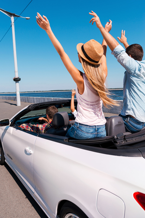Traveling with fun. Rear view of young happy people enjoying road trip in their convertible and raising their arms up photo