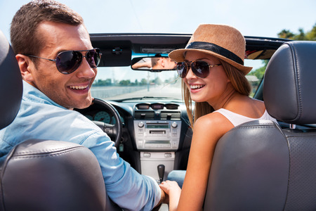 new motor car: Enjoying road trip together. Beautiful young couple enjoying road trip in their convertible and looking over shoulder with smile Stock Photo