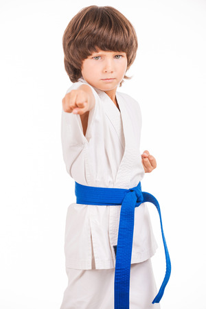 moves: Karate kid. Little boy doing martial arts moves while isolated on white background