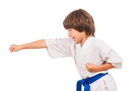 judo: Karate kid. Vista lateral de niño haciendo movimientos de artes marciales, mientras que aislados en fondo blanco Foto de archivo