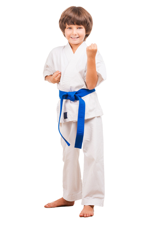 tae: I can defence myself. Full length of little boy in karate uniform standing in karate position while isolated on white