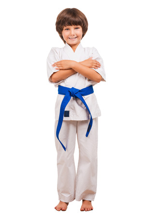 tae: Martial arts boy. Full length of little boy training karate while isolated on white background