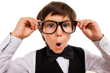 handcarves: Wow! Surprised little boy keeping mouth open and adjusting his glasses while standing isolated on white