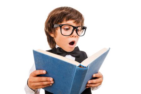 boy book: No way! Wide angle image of surprised little boy reading book and keeping mouth open while standing isolated on white