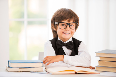 Smart and confident schoolboy. Cute young boy keeping arms crossed while sitting at the table photo