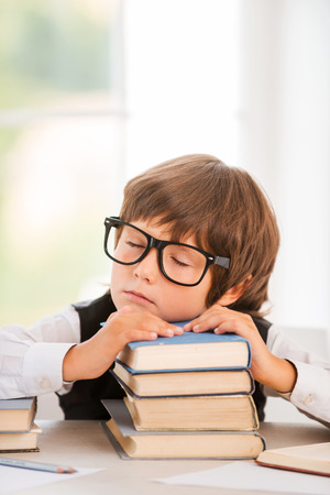 Tired schoolboy. Cute young boy sleeping while sitting at the table and leaning his face at book stack photo