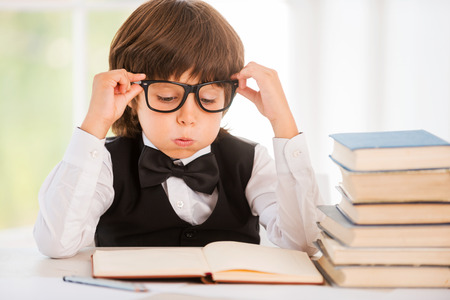 Tired of studying. Tired little boy looking at the book and holding his glasses while sitting at the table photo