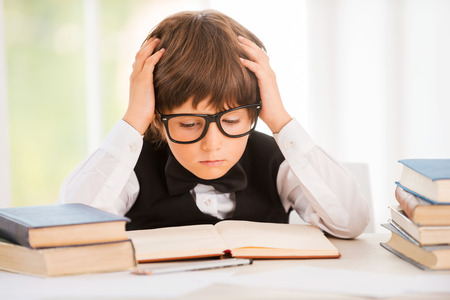 Concentrated on studying. Cute young boy making research while sitting at the desk photo