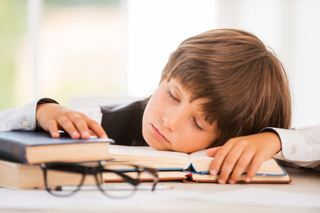 Schoolboy sleeping. Cute little boy sleeping while sitting at the table and leaning his face at the desk  photo