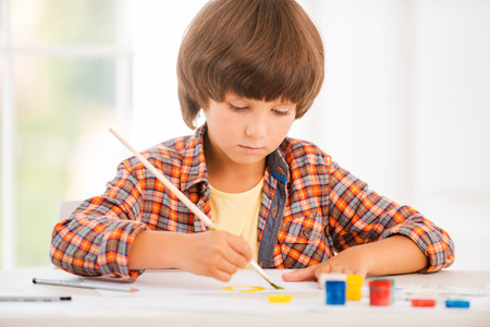 Little artist. Concentrated little boy relaxing while painting with watercolors sitting at the table photo