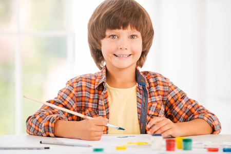 Little artist. Happy little boy relaxing while painting with watercolors sitting at the table photo
