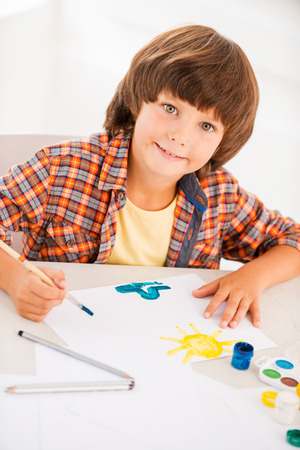 Painting. Top view of little boy relaxing while painting with watercolors sitting at the table photo