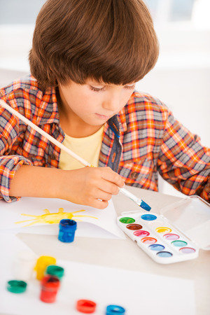 Boy painting. Little boy relaxing while painting with watercolors sitting at the table photo