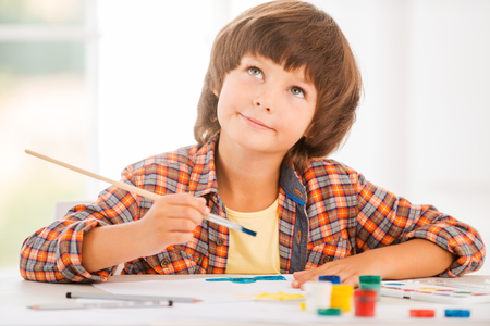 facial painting: Looking for inspiration. Cute little boy relaxing while painting with watercolors sitting at the table