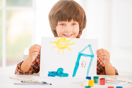 Young artist. Cheerful little boy relaxing while painting with watercolors sitting at the table photo