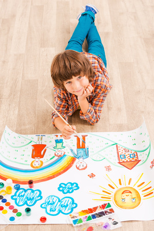 Boy painting. Young boy relaxing while painting with watercolors lying on the floor photo