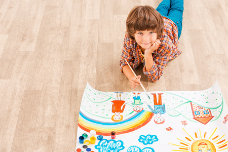 Looking for inspiration. Young boy relaxing while painting with watercolors lying on the floor photo