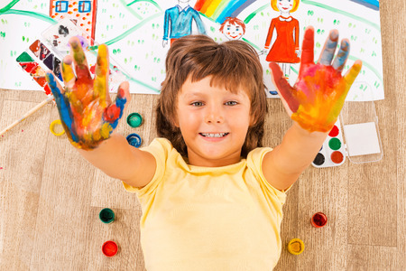 Painted hands. Top view of happy little boy showing his palms coated in colorful paint while lying on the floor photo