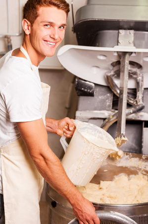 mixing: The best dough for our pastry. Confident young man in apron pushing button on dough mixing machine and smiling