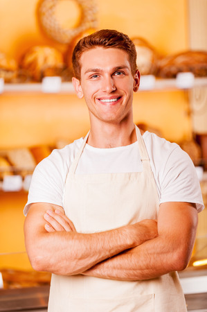 Confident baker. Handsome young man in apron keeping arms crossed and smiling while standing in bakery shop photo