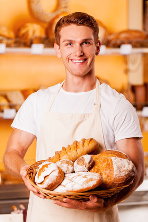 bakery store: Proud of his baked goods. Handsome young man in apron holding basket with baked goods and smiling while standing in bakery shop Stock Photo