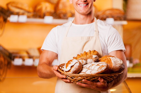 bakery store: The freshest bread for you. Cropped image of young man in apron holding basket with baked goods and smiling while standing in bakery shop