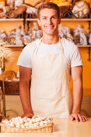 How may I help you? Handsome young man in apron looking at camera and smiling while standing in bakery shop photo