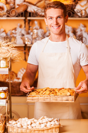 freshest: The freshest cookies for you. Handsome young man in apron holding tray with cookies and smiling while standing in bakery shop