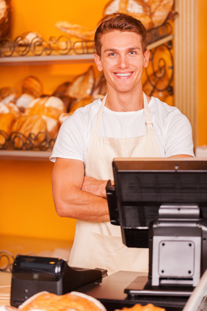 cashier: Cashier in bakery shop. Handsome young male cashier in apron keeping arms crossed and smiling while standing at the cash register in bakery shop