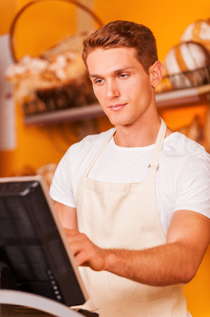 Confident cashier at work. Handsome young male cashier in apron working with cash register while standing in bakery shop  Reklamní fotografie