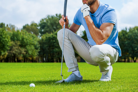 Thinking about next shot. Cropped image of young golfer kneeling near the golf ball and holding hand on chin  Stock Photo