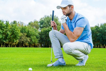 Thinking about the next step. Cropped image of young golfer kneeling near the golf ball and holding hand on chin