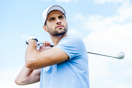 golf cap: Perfect strike. Low angle view of young golfer swinging his driver and looking away with blue sky as background