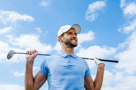 golf glove: Looking towards success. Low angle view of young happy golfer holding driver and smiling with blue sky as background