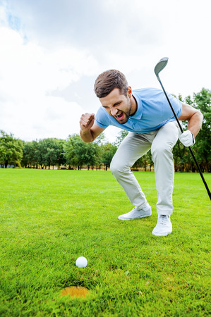 golf glove: Go in! Furious young golfer shouting at the ball while standing on green