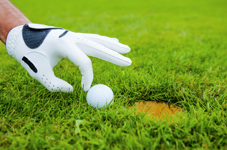 golf glove: Go in! Close-up of male hand in golf glove touching golf ball laying near the hole   Stock Photo