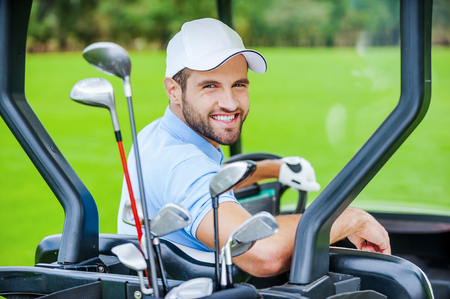 Golfer in golf cart. Rear view of young happy male golfer driving a golf cart and looking over shoulder  photo