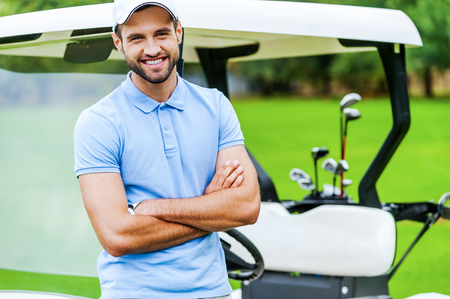 professional man: Golf is my favorite game! Handsome young man keeping arms crossed and smiling while leaning at the golf cart while standing on golf course