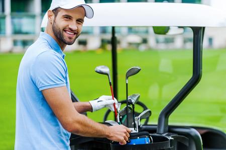 적절한 드라이버를 선택. 골프 카트 근처에 서있는 동안 잘 생긴 젊은 남성 골퍼 드라이버를 선택