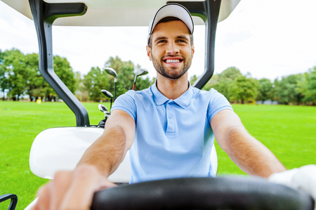 Driving a golf cart. Handsome young man driving a golf cart and looking away photo